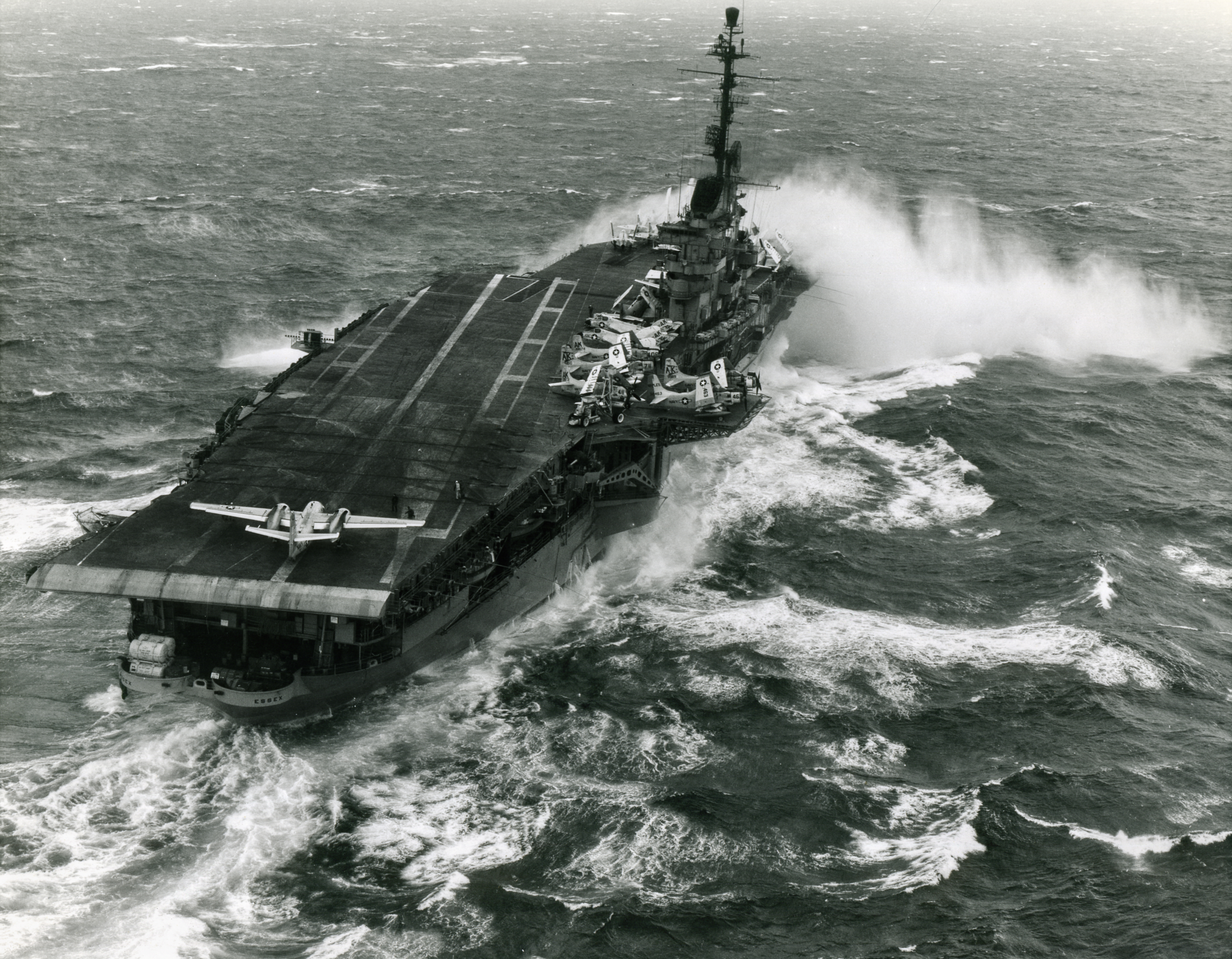 Takes spray over the bow while steaming in heavy seas, 12 January 1960. Note S2F type airplane at the rear of the flight deck, with its engines turning. Other planes visible, amidships, include AD and F4D types. Official U.S. Navy Photograph, from the collections of the Naval Historical Center.
